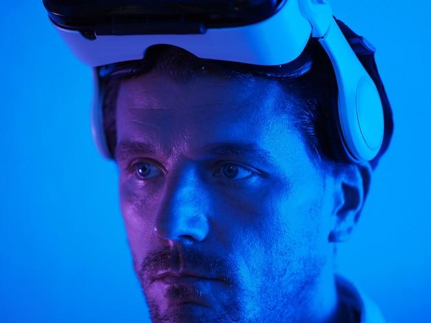 Крупный план. портрет человек виртуальной реальности шлем на голове. неоновый свет вокруг.