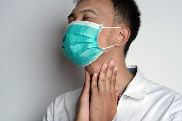 Close up portrait of man wearing health mask having sore throat and touching his neck with hand