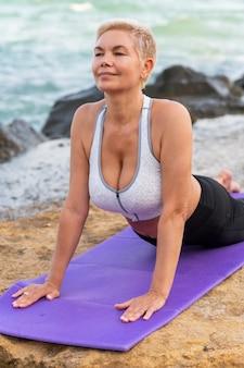 Крупным планом портрет женщины средних лет на берегу моря делают упражнения на растяжку