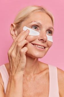 Close up ritratto di donna di mezza età applica cerotti di bellezza sotto gli occhi