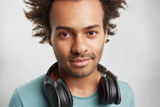 Close up portrait of mixed race dark skinned man with bristle and dark eyes, has headphones
