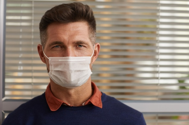 Close up portrait of modern mature man wearing mask and looking at camera against office blinds background, copy space