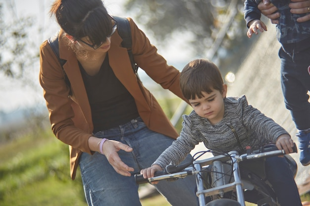 Close up portrait of mom teaches the child to ride a bike