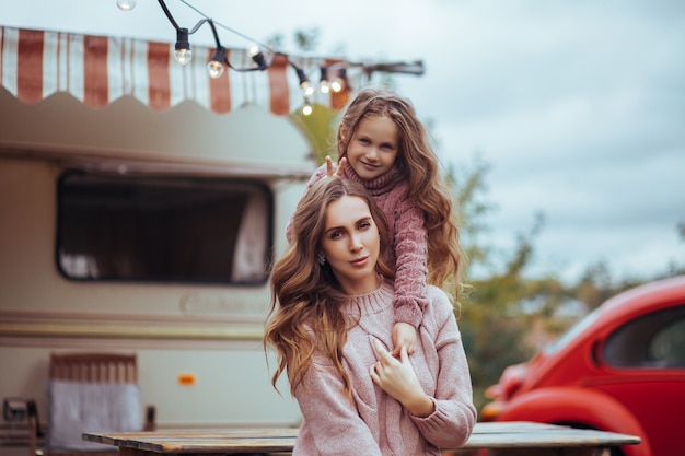 Close up portrait of mother and little daughter hugging and relaxing in countryside on camper van vacation