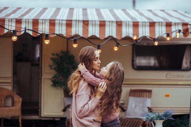 Close up portrait of mother and little daughter kissing and having fun in countryside on camper van vacation
