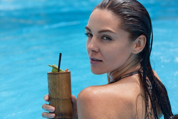 Close up portrait of mysterious attractive young woman swimming in swimming pool, spending her weekends at spa resort, looking aside, chilling with cocktail in one hand. people and rest concept.