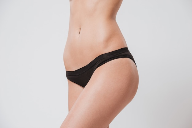 Close up portrait of a naked woman body in black panties isolated on white surface