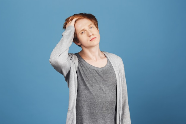 Close up portrait of narcissistic young good-looking guy with ginger hair in casual grey outfit fixing hair with hand,  with confident and flirty face expression.