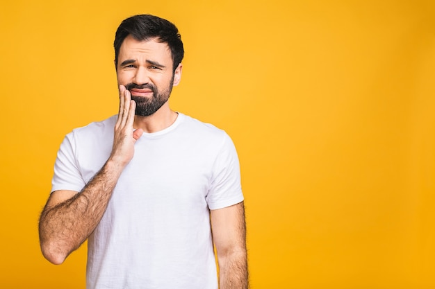 Close up portrait of nervous unhappy troubled handsome bearded man touching his cheek he has toothache isolated on yellow background copyspace.