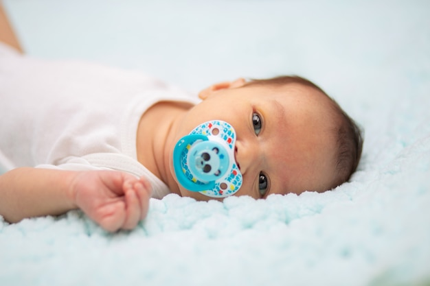 Close-up portrait of a newborn baby with a pacifier in his mouth