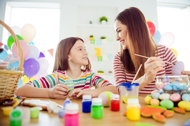 Close-up portrait of nice attractive cheerful cheery girls small little daughter creating festal festive decorative elements april day spending time in white light interior room house indoors