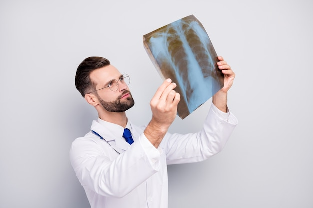 Close-up portrait of nice attractive focused doc holding in hand looking at lungs shot cancer illness disease problem prevention isolated on light white gray pastel color