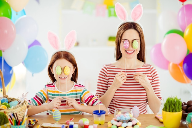 Close-up portrait of nice attractive funky creative cheerful girls small little pre-teen sister wearing bunny ears covering eyes with decorative eggs in white light interior room house