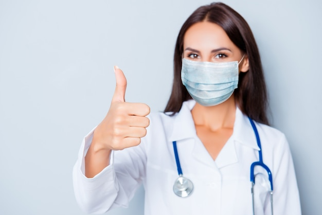 Close-up portrait of  nice attractive healthy lady intern wearing gauze safety mask ncov mers pandemia disease prevention concept showing thumbup isolated gray background