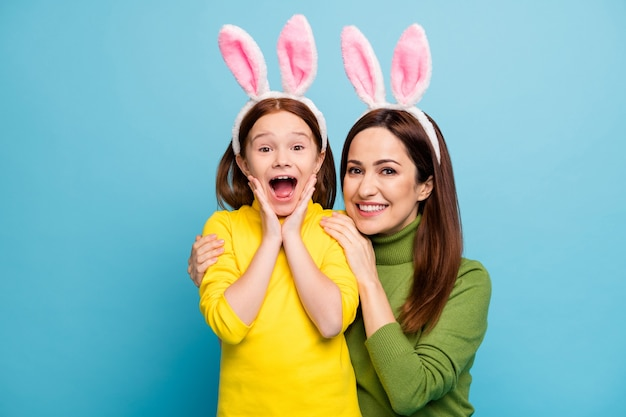 Close-up portrait of nice attractive lovely amazed cheerful cheery girls mom mum mommy wearing rabbit ears having fun isolated over bright vivid shine vibrant blue color