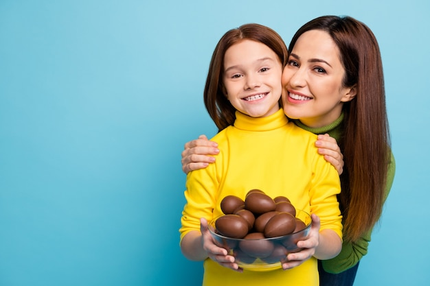 Close-up portrait of nice attractive lovely charming kind careful cheerful cheery girls holding in hands sweet eggs hugging isolated over bright vivid shine vibrant blue color