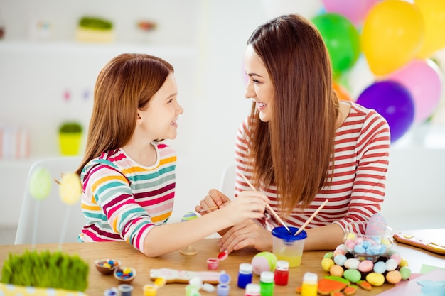 Close-up portrait of nice attractive lovely creative cheerful cheery girls small little daughter creating artwork handicraft spending time day april in white light interior room house indoors