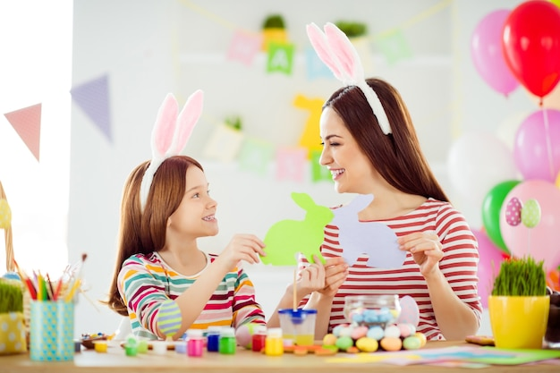 Close-up portrait of nice attractive lovely creative cheerful cheery girls small little daughter wearing bunny ears having fun creating making handicraft in white light interior room house