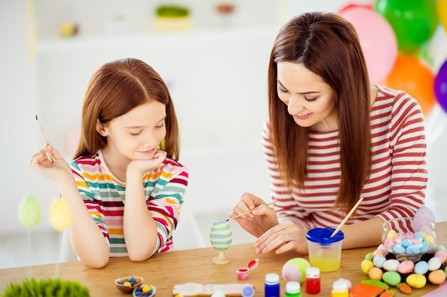 Close-up portrait of nice attractive lovely foxy ginger cheerful cheery girls small little daughter creating handicraft artwork april in white light interior room house indoors