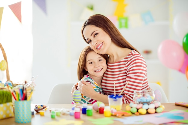 Close-up portrait of nice attractive lovely gentle affectionate sweet cheerful cheery girls small little daughter making handicraft spending day embracing in white light interior room house indoors