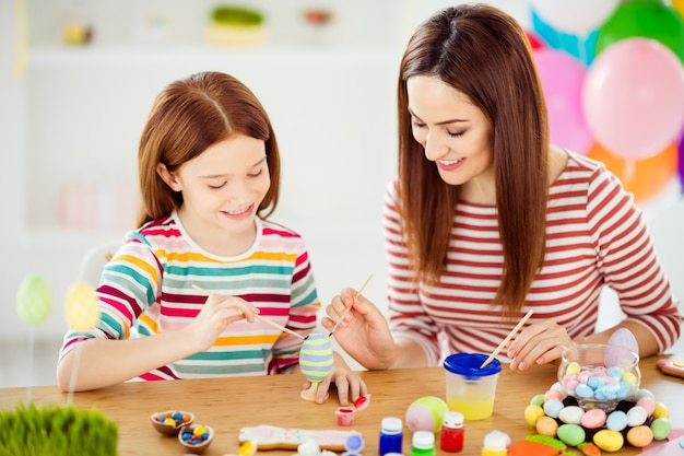 Close-up portrait of nice attractive lovely winsome cheerful cheery girls small little daughter creating handicraft handiwork in white light interior room house indoors