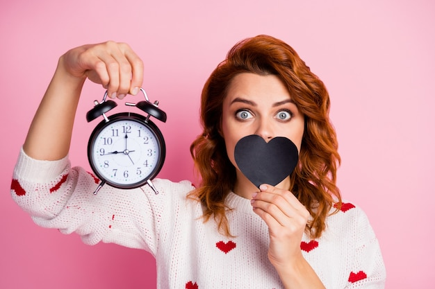 Close-up portrait   nice attractive pretty cute lovely funny foxy  girl holding in hand bell clock closing mouth with black heart