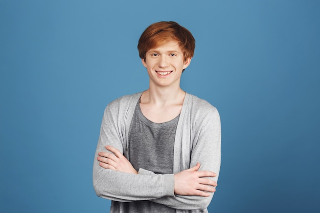Close up portrait o young attractive cheerful red-haired male student in casual grey outfit smiling with teeth, crossing hands,  with confident and happy expression.