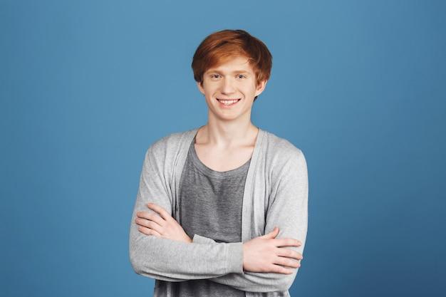 Крупным планом портрет o молодой привлекательный веселый рыжий мужчина студент в случайный серый наряд, улыбаясь с зубами, скрещивая руки, с уверенным и счастливым выражением.