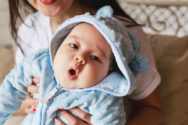 生後2ヶ月の新生児混血アジア人白人少年のクローズアップ肖像画。自然な屋内照明。クールなトーン