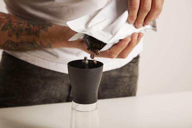 현대 작은 버 그라인더에 커피 콩을 붓는 흰색 티셔츠와 청바지 바리 스타의 초상화를 닫습니다