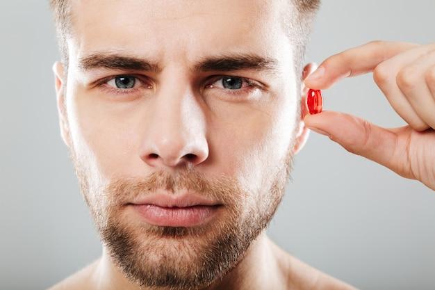Крупным планом портрет бородатый мужчина держит красную капсулу