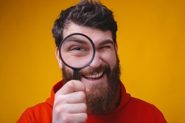 黄色の空間に虫眼鏡を通して見るひげを生やした男の肖像画を閉じます。