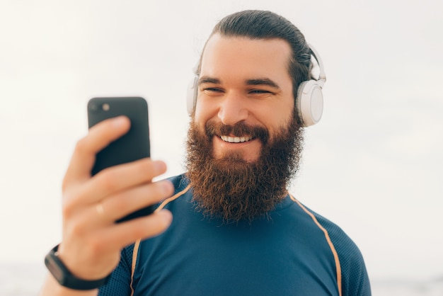 スポーツtシャツとヘッドフォンを身に着けているひげを生やした男の肖像画をクローズアップは彼の携帯電話を見ています。