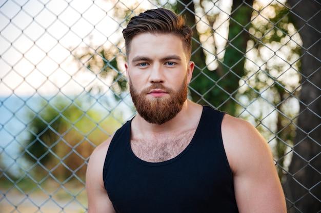 立って、屋外で正面を見ているひげを生やした若い男の肖像画をクローズアップ