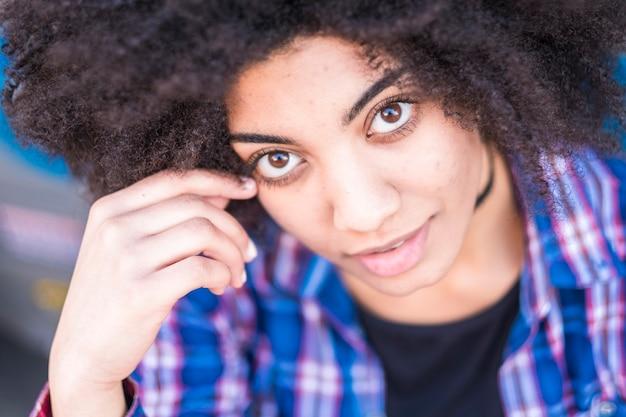 미소하고 당신을보고 아름다운 흑인 여성의 초상화를 닫습니다