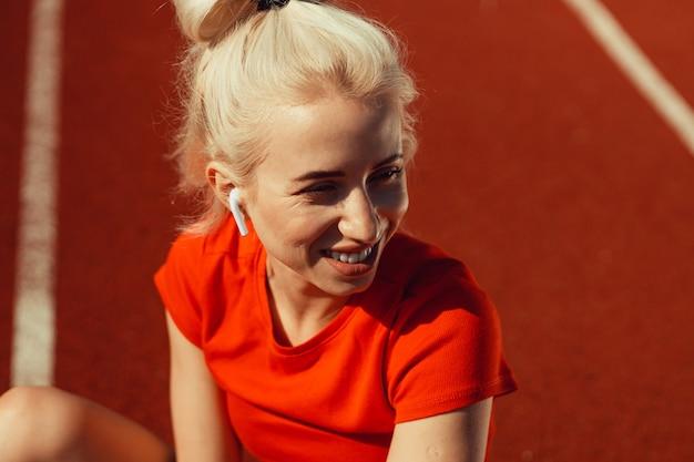Крупным планом портрет красивой блондинки, сидящей на беговой дорожке