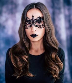 ハロウィーンパーティー中にポーズをとって魔女の衣装で美しいブルネットの女性の肖像画をクローズアップ