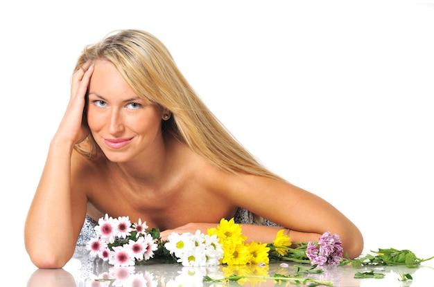 Крупным планом портрет красивой женственной молодой блондинки, позирующей с букетами цветов на белом в студии
