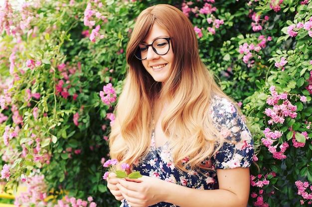 バラの庭で美しい少女の肖像画をクローズアップ