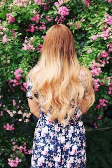 カラフルな花の近くに立っているヴィンテージドレスの美しい少女の肖像画をクローズアップ