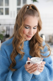 キッチンの青いセーターの髪型を持つ美しい幸せなかわいい女の子のクローズアップの肖像画