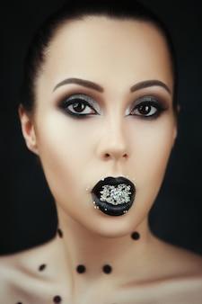 暗い化粧品で美しいモデルのクローズアップの肖像画