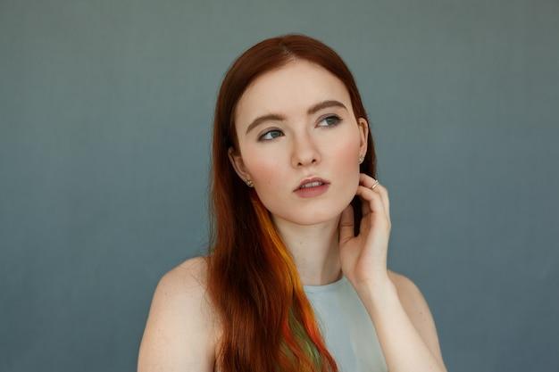 髪の色のストランドと思慮深い真面目な表情をした緑色の目、そして口を大きく開いた美しい赤毛の女性モデルの肖像画をクローズアップします。青い壁にポーズをとってかわいい生姜の女の子