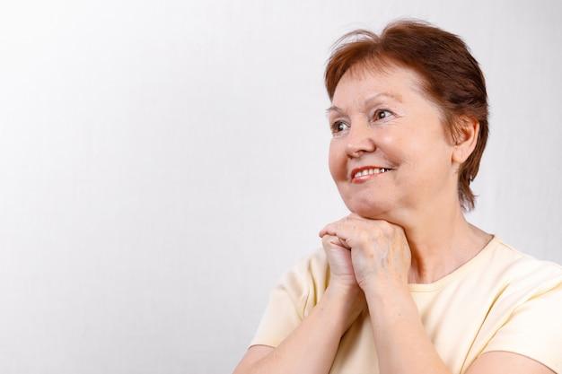 軽いtシャツで白の側にいる美しい年配の女性のクローズアップの肖像画。孤立した