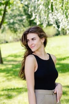 屋外の茶色の髪の美しい笑顔の少女の肖像画を閉じます。