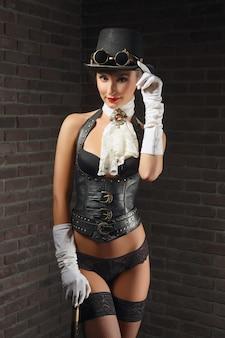 Портрет конца-вверх красивой девушки steampunk в женское бельё и чулках, шляпе и изумлённых взглядах.