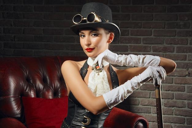 Портрет конца-вверх красивой девушки steampunk в женское бельё и чулках сидя в старом кресле.