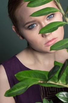 緑の花の後ろに彼女の顔を隠している美しい女性のクローズアップの肖像画。