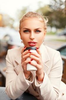 거리에 세련된 코트에 커피와 함께 아름 다운 여자의 근접 초상화