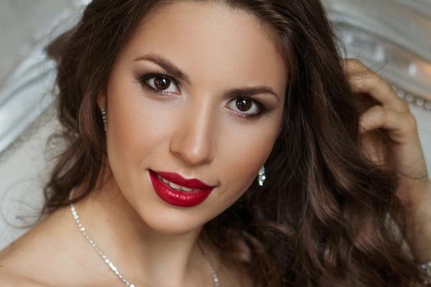 化粧と赤い唇、美しい髪の美しい女性のクローズアップの肖像画